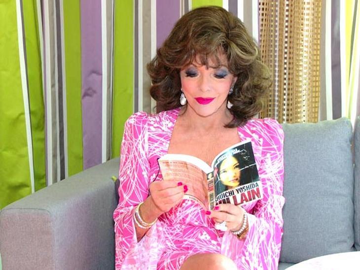 """Joan Collins: Was eine Diva in der Handtasche haben sollte...Ein Buch mit dem Titel """"Bösewicht""""Ob dieses Buch als """"Handbuch"""" für eine Diva taugt? Entsetzt greift Joan Collins zu dem Buch und fragt: """"Ist das ein Porn"""
