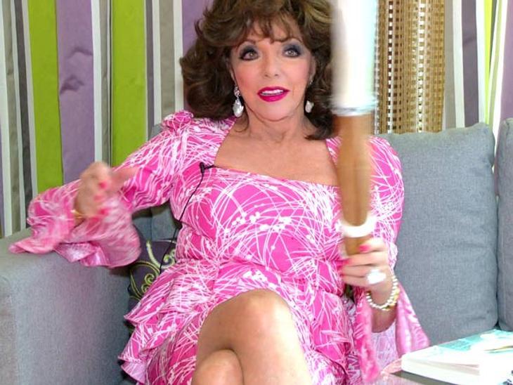 """Joan Collins: Was eine Diva in der Handtasche haben sollte...Joan Collins schwingt das Schwert ein paar Mal hin und her. Doch ein wenig unpraktisch ist es schon und zu groß für die Handtasche. """"Es ist einfach zu groß. Und wenig feminin"""
