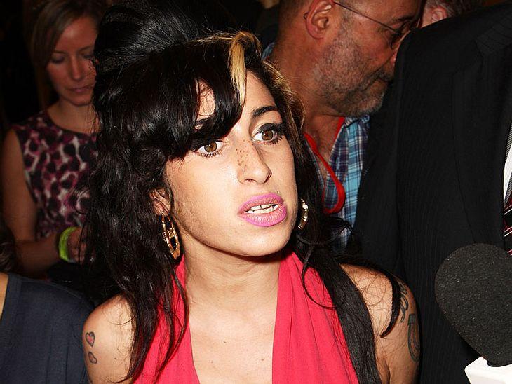 """Mehrere Flaschen Wein und heiße Pizzas """"von guter Qualität"""" gehören zu den Standardforderungen von Amy Winehouse, wenn sie irgendwo auftritt. Falls die Pizzas ihren Erwartungen nicht entsprechen, trägt der jeweilige Veranstalter d"""