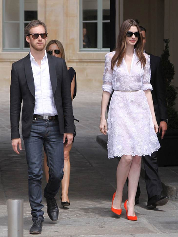 Black and White - Der Style von Anne HathawayFür einen Shoppingbummel mit ihrem Ehemann Adam Shulman durch Paris wählte die 29-Jährige ein sommerliches weißes Spitzenkleid. Die feuerroten Pumps setzen einen farblichen Akzent.