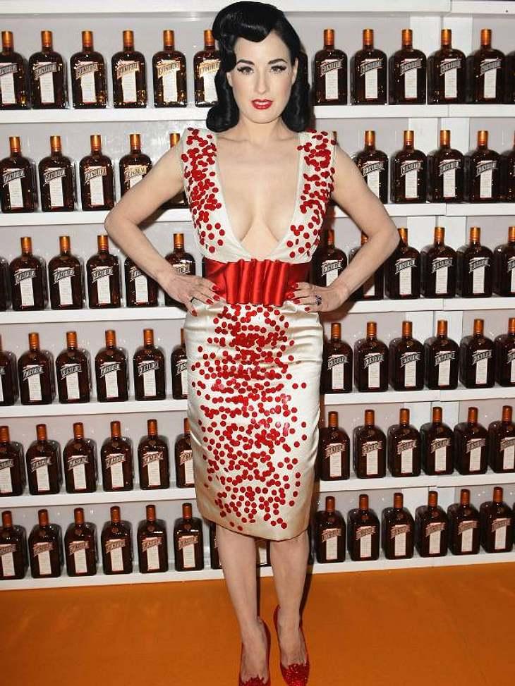 Pailletten-Abendkleider:Dita von Teese ist, was wie sonst nicht von ihr kennen, sehr zurückhaltend mit den pailletten an ihrem Kleid, dafür sind sie umso größer und leuchten in strahlendem Rot.