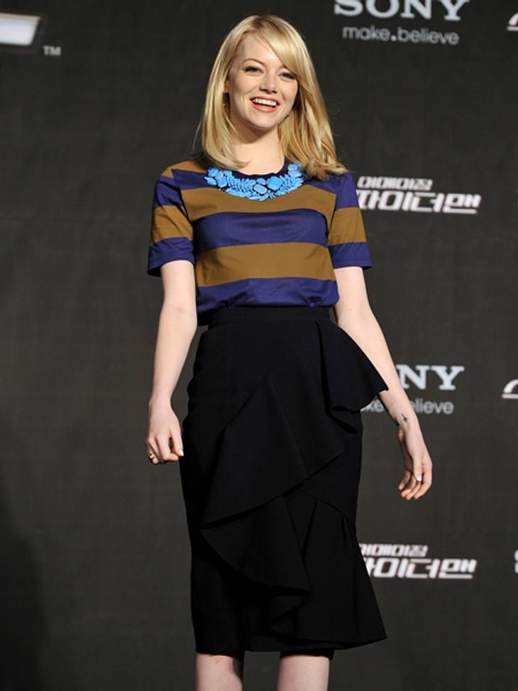 Der extravagante Look von Emma StoneLässig aber schick wirkt die Kombi aus navyblau-olivgrün gestreiftem Shirt und türkisfarbener Kette zum schwarzen knielangen Rock.
