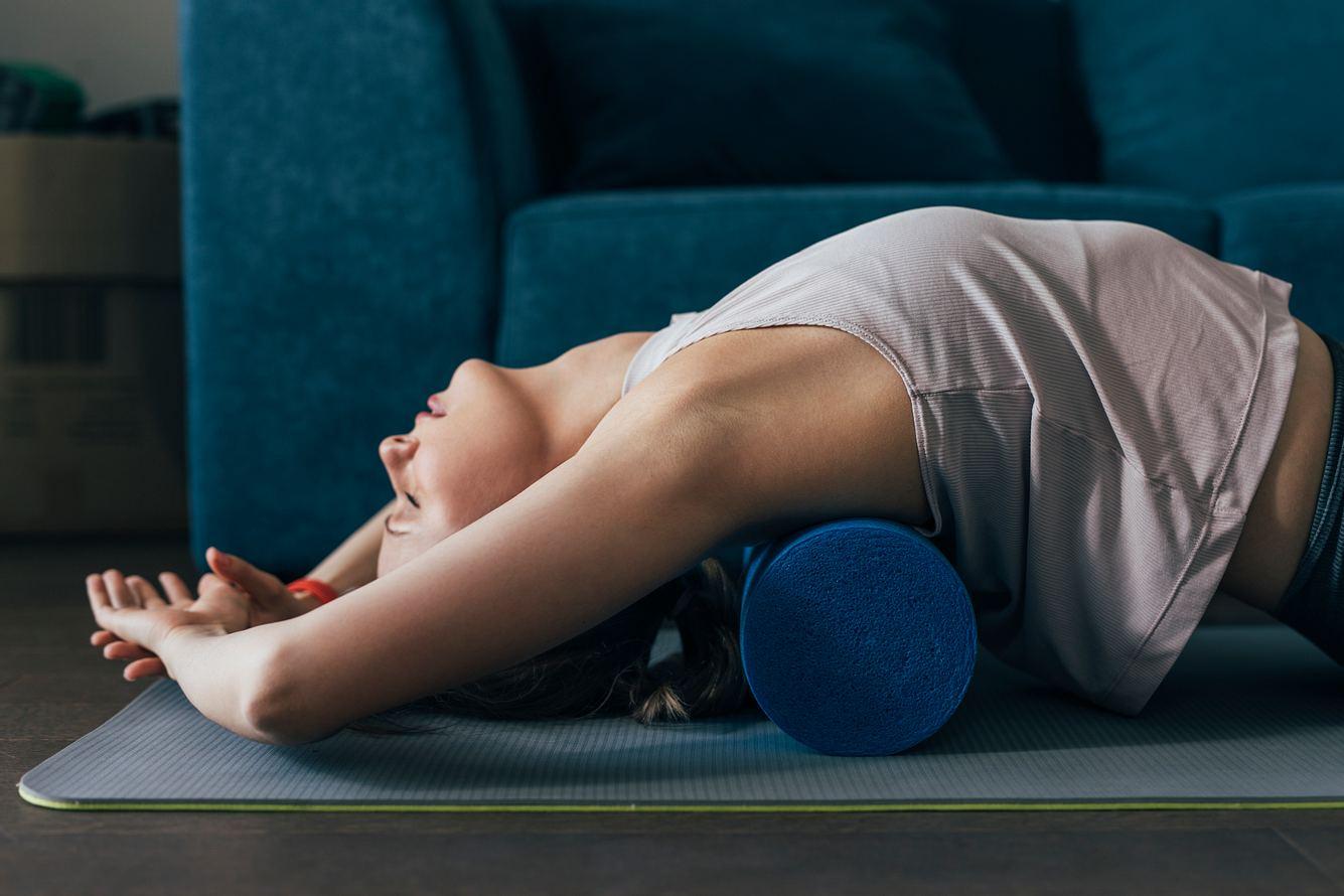 Frau macht Übungen mit einer Faszienrolle für den Nacken.