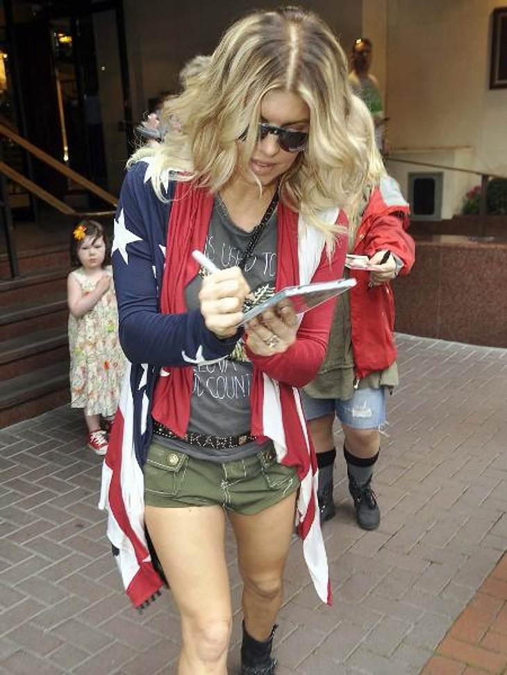 """Die Promis stehen auf Stars and StripesNoch schnell auf dem Weg eine CD signieren - kein Problem für """"Black Eyed Peas""""-Frontfrau Fergie (37) in ihrem lässigen Stars and Stripes-Cardigan."""
