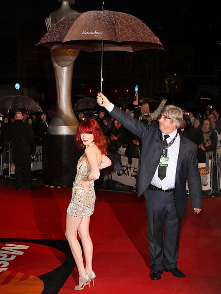Stars und ihre Regenschirm-HalterPosen und trotzdem nicht nass werden - Florence Welch hat da so ihre Tricks und ihren eigenen Regenschirm-Halter.