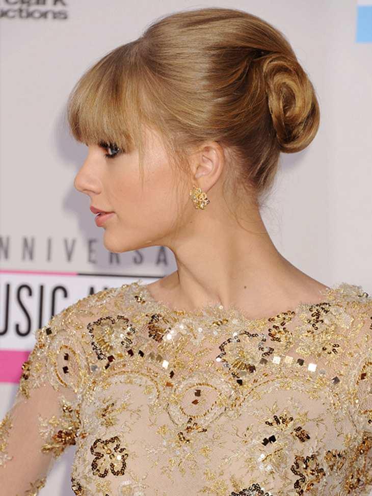 Die Schlank-Frisuren der Stars,Mit dieser lockeren Hochsteckfrisur macht Taylor Swift (23) vor, wie man sich perfekt schlank schummelt. Steckt man die Haare besonders weit oben am Hinterkopf hoch, wird das Gesicht optisch gestreckt.