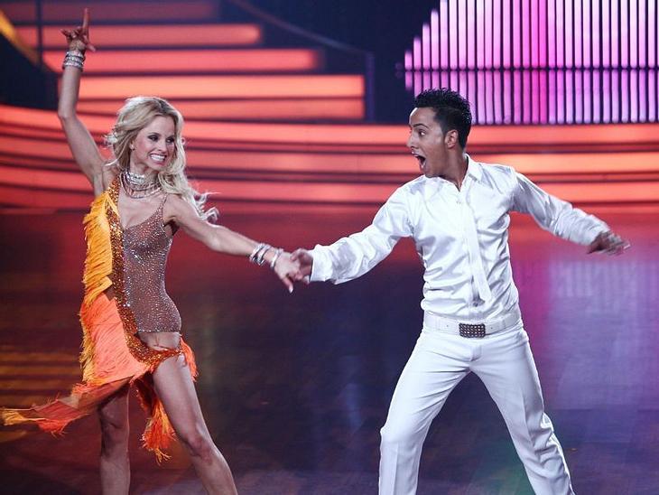 """Let's Dance: Das Halbfinale, """"Der Checker"""" , ganz in weiß gekleidet, versuchte in die Fußstapfen von John Travolta zu treten. Seine Samba zu """"Stayin' Alive"""" brachte ihm 26 Punkte ein. Alle Infos zu """"Let's Dance&quot"""