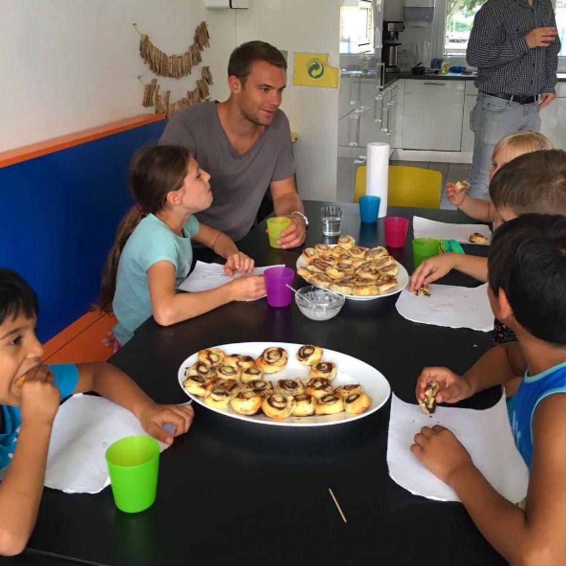 Manuel Neuer isst Zimtschnecken mit Kindern
