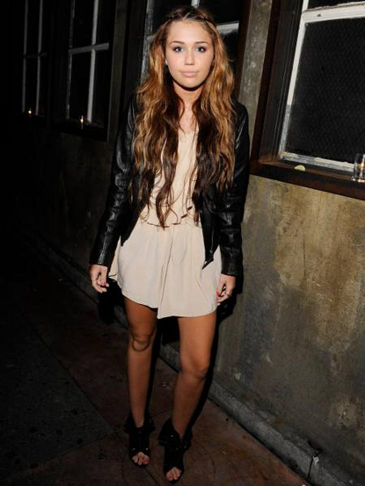 Vom Girlie zum Punk Chick: Der Look von Miley CyrusMai 2010: Cooler Stilbruch - auf einer Party in Los Angeles erscheint Miley lässig in Kleid und Lederjacke.