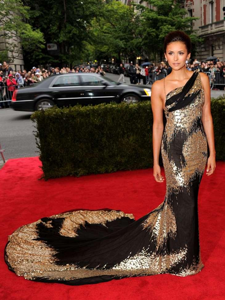 Elegant & sexy - Der Style von Nina DobrevDie schwarz-goldene Abendrobe mit opulenter Schleppe passt perfekt zur gebräunten Haut der Schauspielerin.