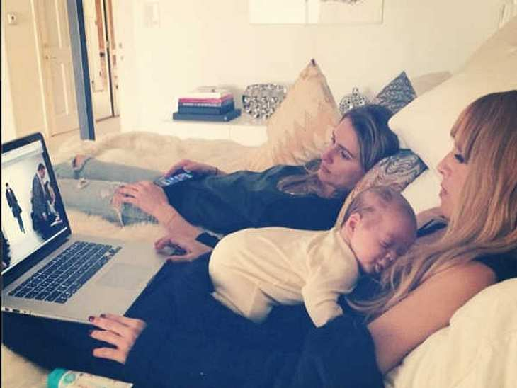 Dieses Bild ist der Inbegriff für Working Mum und Multitasking! Star-Stylistin Rachel Zoe kuschelt ihren jüngsten Spross Kaius und macht nebenbei ihre Arbeit am Laptop.