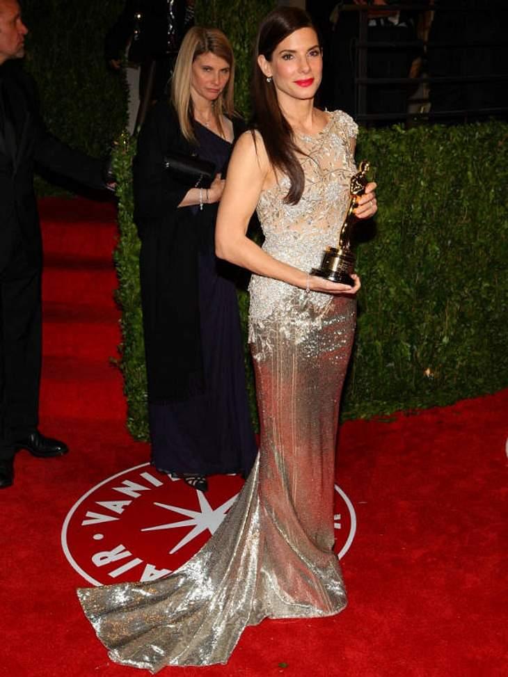 The Golden Dress! Sandra Bullock im metallenem Glückskleid. Ihr schönstes Accessoires? Der Goldjunge in ihren Armen!