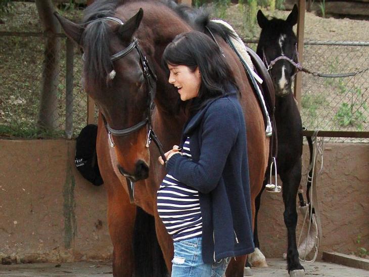 Schwangere Stars Selma Blair ist zum ersten Mal schwanger und genießt ihre Schwangerschaft total. Hier kuschelt sie ihren Bauch und ein Pferd.