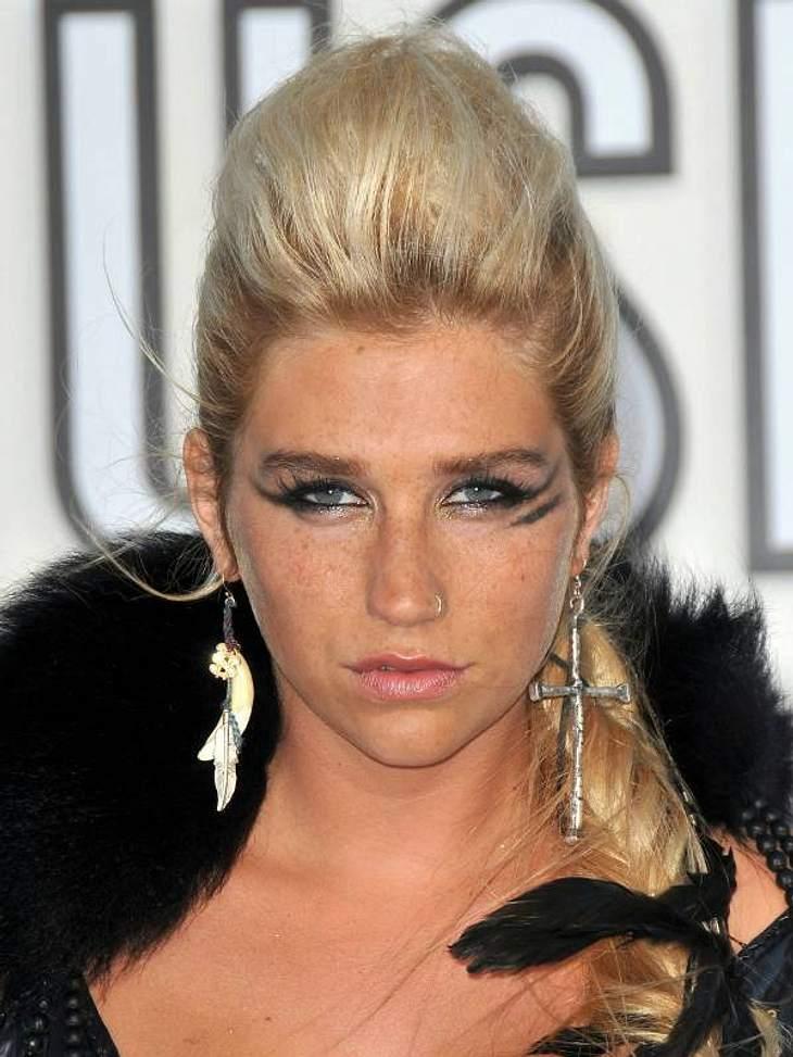 Teenie-Schreihals Kesha hält nichts von klassischer Eleganz und schaut motzig in die Kameras, während ein silbernes Kreuz im XXL-Format an ihrem Ohr baumelt. Dieses Outfit erinnert eher an einen Raaben-Kostüm, als an feminine Abend-Gaderobe