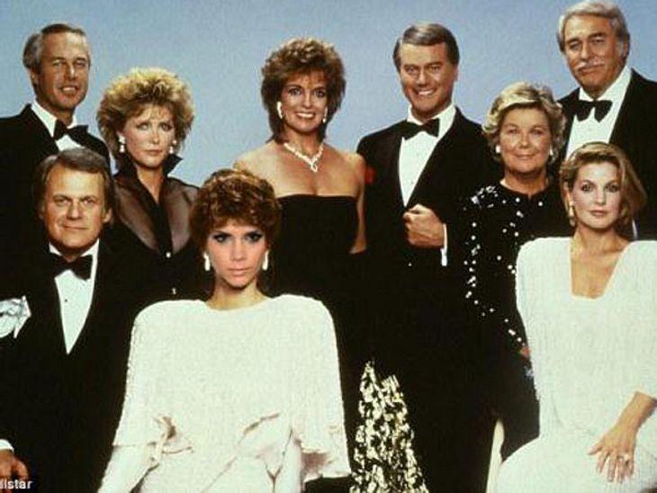 """Finde den Fehler! Auf dieses Gruppenbild der """"Dallas""""-Stars hat sich eine geschlichen, die da eigentlich gar nicht hingehört...Wer genau hinschaut, erkennt ganz vorne im cremefarbenen 80ies-Kostüm und mit flotter Dauerwelle Design"""