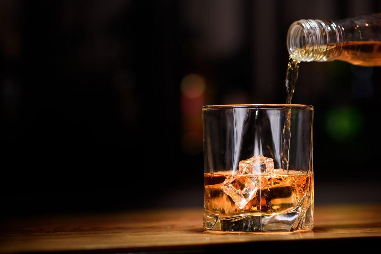 Whisky wird in ein Whisky Glas gegossen.